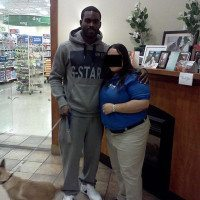 Michael Vick posing with a PetSmart employee and his puppy, Angel.