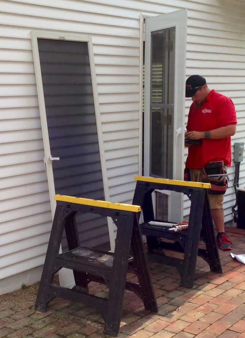 The storm door with the installed Plexidor being hung by Mr. Handyman.